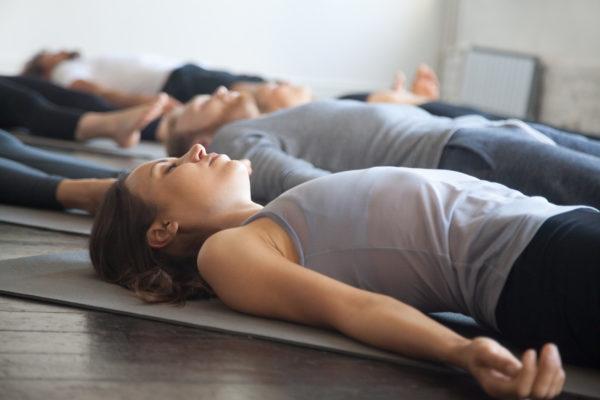 Kursteilnehmer liegen am Boden auf der Matte und werden in einer Entspannungsübung angeleitet